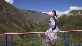 A girl making selfie on a background of mountains and forests. A girl in a dress makes selfie against the backdrop of mountains and forests. Beautiful nature stock video footage