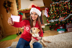 Girl making selfie with nice puppy. Young girl making selfie with nice puppy on Christmas eve royalty free stock photo