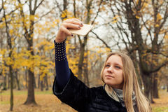 Girl making selfie in a park in autumn Stock Image
