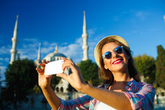 Girl making selfie by the smartphone on the background of the Bl Stock Image