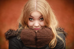 Girl making silly faces. Fun cheer playing forest nature outdoor concept. Girl making silly faces. Young blonde lady in winter clothing covering her face with Royalty Free Stock Photography