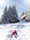 Girl making snow angel Stock Image