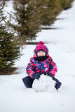 Girl making snowball for a snowman at winter Stock Images