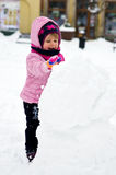 Girl making snowman. Cute little girl making a snowman in a city square Stock Image