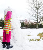 Girl making snowman in garden Royalty Free Stock Image