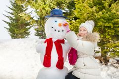 Girl making snowman putting carrot as his nose Royalty Free Stock Photography