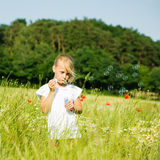 Girl making soap bubbles. Little girl in a field making soap bubbles and having fun with it royalty free stock photos