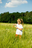 Girl making soap bubbles. Little girl in a field making soap bubbles and having fun with it royalty free stock images