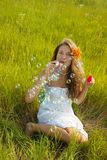 Girl making soap bubbles on   grass Royalty Free Stock Images