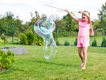 Girl making soap bubbles in home garden royalty free stock photography