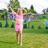 Girl making soap bubbles in home garden stock image