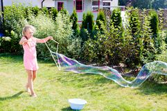Girl making soap bubbles in home garden stock photos