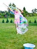 Girl making soap bubbles in home garden stock photo