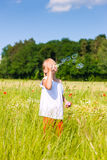 Girl making soap bubbles Stock Photo