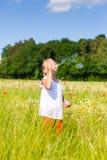 Girl making soap bubbles Stock Photo