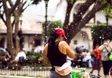 Girl making soap bubbles on market in Guatemala Stock Images