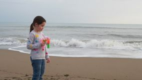 Child making soap bubbles playing at sea. Outdoor beach activity for children. Girl making soap bubbles playing at sea. Outdoor beach activity for children stock video footage