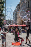 Girl making soap bubbles on a sunny day on the street in Berli Stock Photography