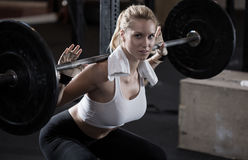 Girl making squat with barbell Stock Images