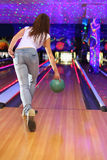 Girl making throw of ball in bowling club. Spin of girl wearing jeans and white T-shirt making throw of green ball in bowling club royalty free stock photo