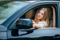 Girl making up into a car. Stock Photos