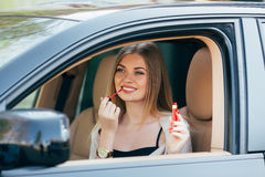 Girl making up into a car. Stock Image