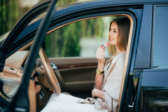 Girl making up into a car. Royalty Free Stock Image
