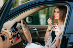 Girl making up into a car. Royalty Free Stock Images