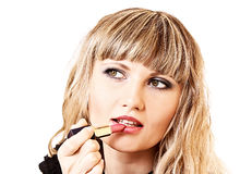 Girl making up her lips with lipstick Royalty Free Stock Image