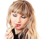 Girl making up her lips with lipstick Royalty Free Stock Photos