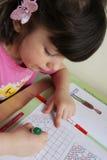 Girl making up for homework Stock Images