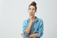 Girl making up plan what to do next. Portrait of thoughtful curious woman with bun hairstyle, holding fingers on lips. While looking aside and thinking about Royalty Free Stock Image