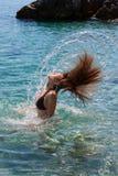 Girl making water splash Stock Images