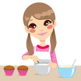 Girl Making Whipped Cream. Cute little girl with apron making whipped cream for cupcakes isolated on white background Stock Images