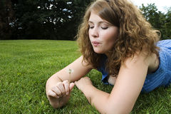 Girl making a wish. Laying in the grass in a park Stock Images