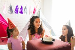 Girl Making A Wish While Friends Celebrating Her Birthday. During sleepover party at home stock photo
