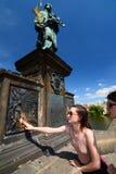Girl making a wish. Statue of St. John of Nepomuk. Charles Bridge. Prague. Czech Republic Stock Image