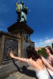 Girl making a wish. Statue of St. John of Nepomuk. Charles Bridge. Prague. Czech Republic Royalty Free Stock Image