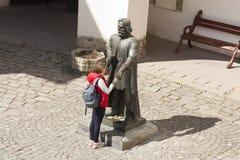 Girl making a wish to statue of prince Podolsky Fedir Koryatovych 1331-1414 in castle Palanok, Mukachevo, Ukraine photo: MUKACHE Royalty Free Stock Photo
