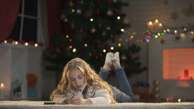 Girl making wishlist before Christmas eve, writing letter to Santa Claus, magic. Stock footage stock video