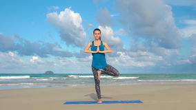 The girl is making yoga pose on beach in Vietnam. Sea or ocean happy woman relaxation. Water and waves. Hands and blue Royalty Free Stock Photos