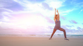 The girl is making yoga pose on beach in Vietnam. Sea or ocean happy woman relaxation. Water and waves. Hands and blue Stock Photo