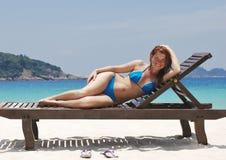 Girl on a Maldive beach. Taking a bikini sunbath on a deck in tropic beach at Maldive Island Stock Photo