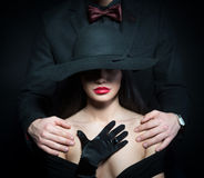 Girl with the male arms on her shoulders. Portrait of a women in big black hat and a men putting his arms on her shoulders Stock Images