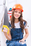 Girl in male role is upholding a saw Stock Images