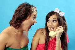 Girl maliciously yells on girl that call phone. Girl with brunet short hair, yelling at the girl in the red dress and white bow on her head that holds phone in Royalty Free Stock Photo