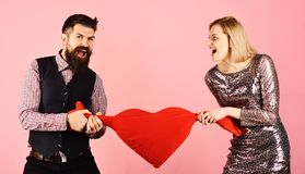 Girl and man with angry faces play with toy heart. Girl and bearded men with angry faces play with soft toy heart with hands. Relationship break concept stock photo