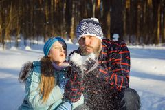 Girl and man blowing on the snow. Girl and men blowing on the snow in winter in the forest Royalty Free Stock Photo