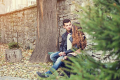 Girl man couple sitting autumn park Royalty Free Stock Photography