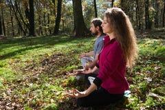 Girl and man doing yoga meditation Royalty Free Stock Photos